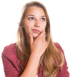 Eine junge Frau hat die rechte Hand am Kinn und schaut zweifelnd.